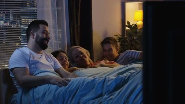 Family In Bed Watching TV: Stock Video