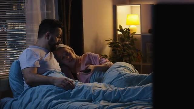 Couple In Bed Watching TV: Stock Video