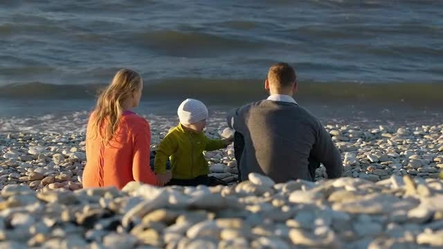 Young Family On Pebble Beach: Stock Video