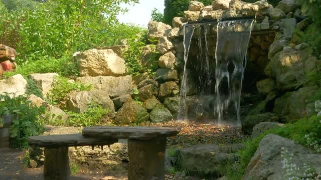 Man-Made Waterfall And Park Bench: Stock Video