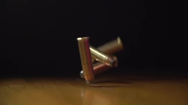 Bullets Faling On Wooden Table: Stock Video