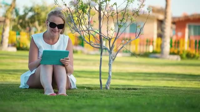 Beautiful Woman Sitting On Lawn: Stock Video