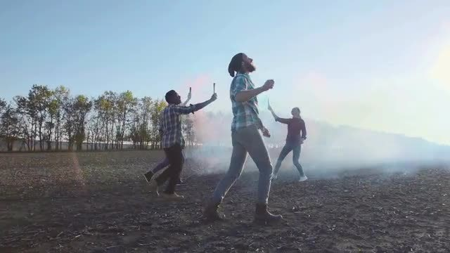 Friends Enjoying Colored Smoke Grenades: Stock Video