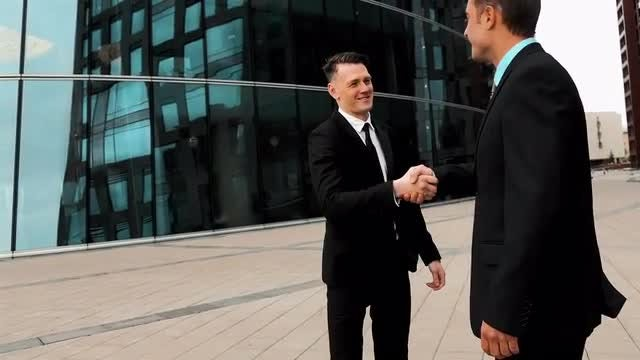 Two Businessmen Exchanging A Handshake: Stock Video