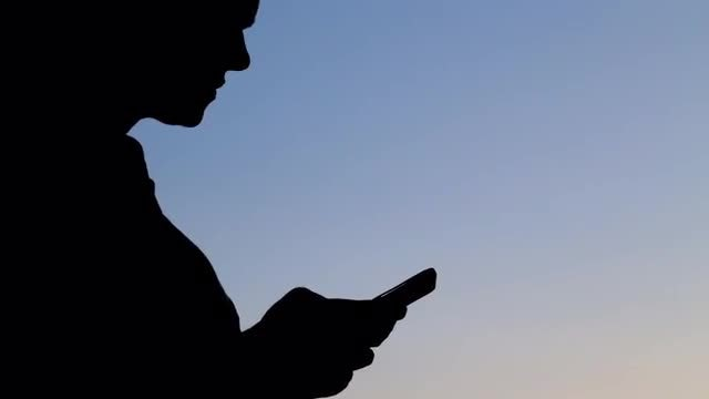 Silhouette Of A Woman Texting: Stock Video