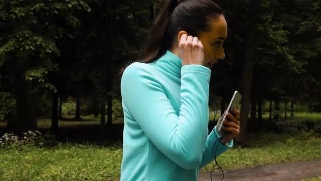 Sporty Woman in Headphones Running: Stock Video