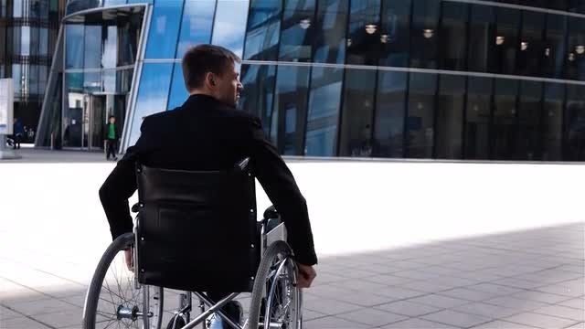 Disabled Businessman Riding A Wheelchair: Stock Video