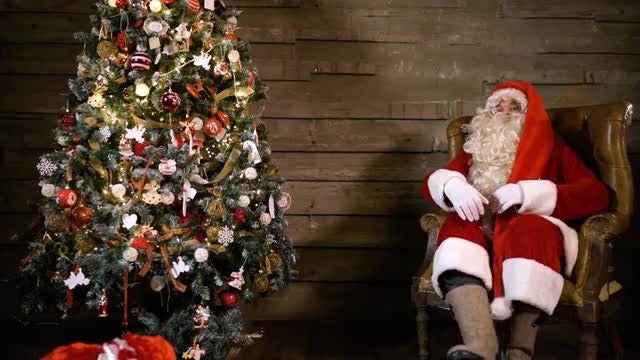 Santa Claus Sitting By Tree: Stock Video