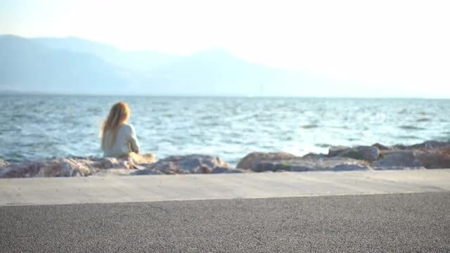 Woman Sitting On Shoreline: Stock Video