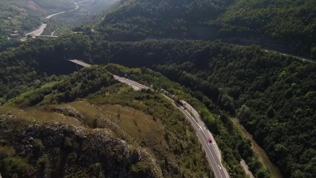 Red Car Tracking In Mountains: Stock Video