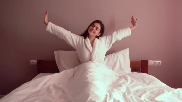 Beautiful Woman Stretches In Bed: Stock Video