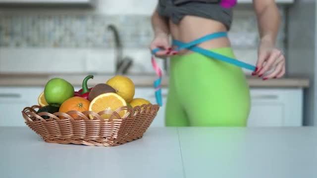 Woman Measuring Waist In Kitchen: Stock Video