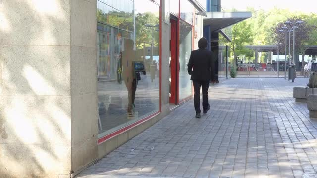 Businessman Walks On Commercial Street: Stock Video