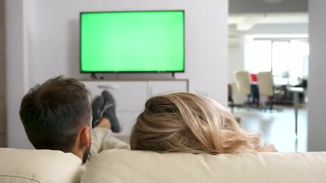 Couple On Couch Watching TV: Stock Video
