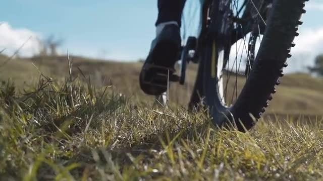 Biking Up The Grassy Hill: Stock Video