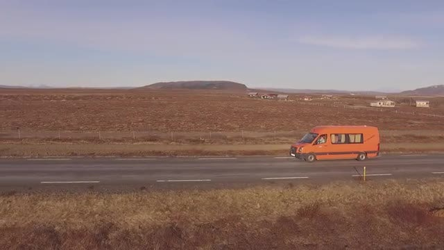 Orange Van Cruising Iceland Road: Stock Video