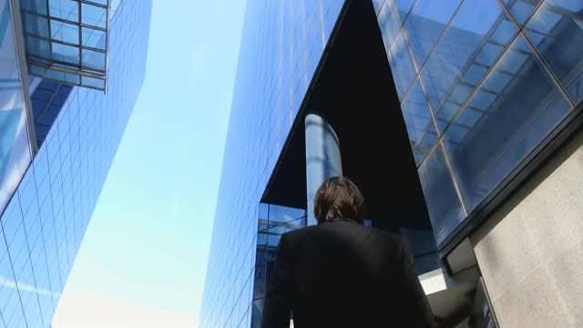 Businessman Walking By Glass Buildings: Stock Video