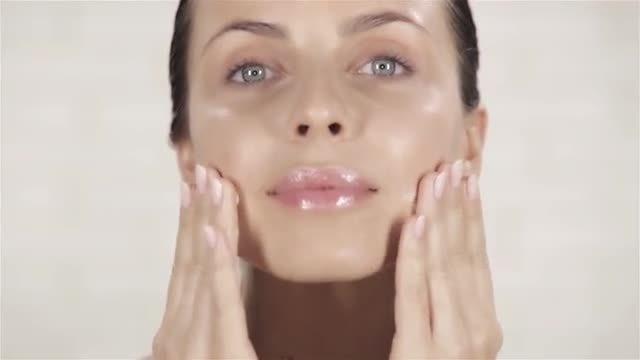 Young Woman Applying Facial Cream: Stock Video
