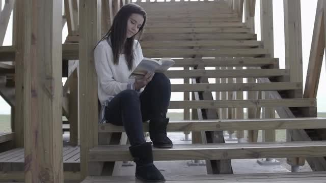Beautiful Woman Reading Outdoors: Stock Video