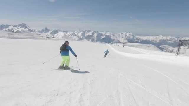 Two Skiers Descending A Mountain: Stock Video