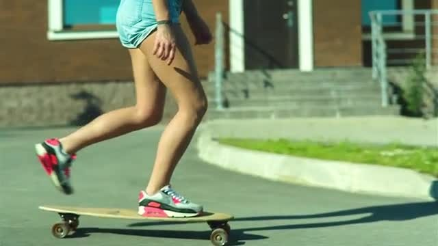 Girl Skateboards Past Apartments: Stock Video