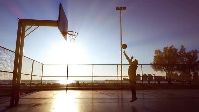 Man Playing Basketball At Sunset: Stock Video