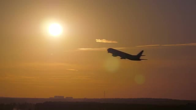 Airplane Takeoff Passing Through Sunset: Stock Video