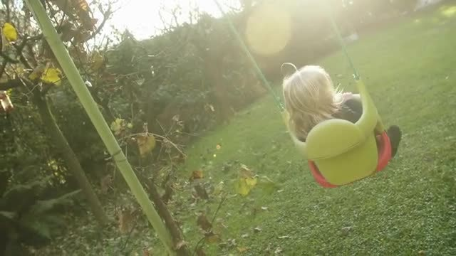 Baby Swinging Against The Sun: Stock Video