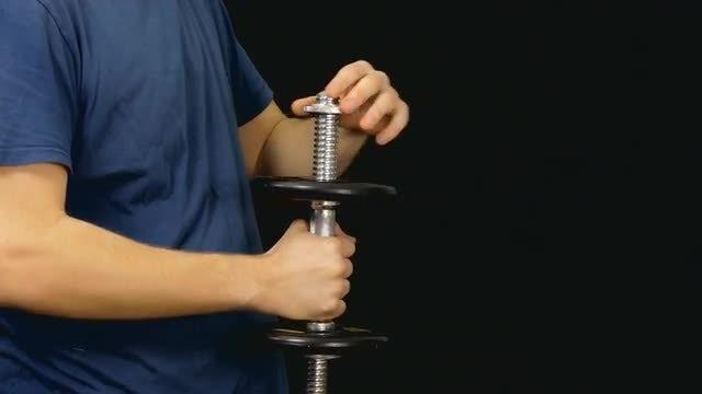 Man Assembling A Dumbbell: Stock Video