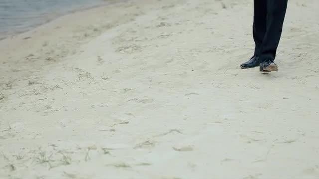Groom Walks Along Shore: Stock Video