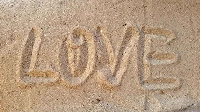 Writes Love In Sand: Stock Video