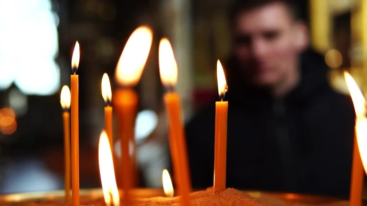 Man Prays Near Candles: Stock Video