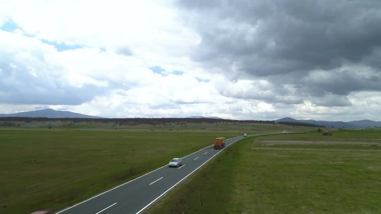 Trucks Drive On Rural Road: Stock Video