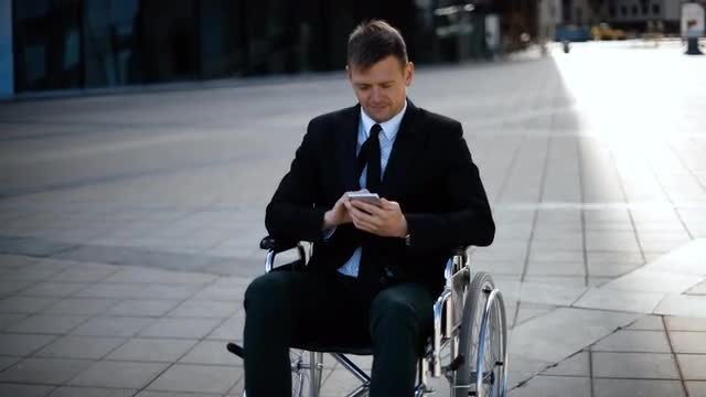 Handicapped Man Uses Phone: Stock Video