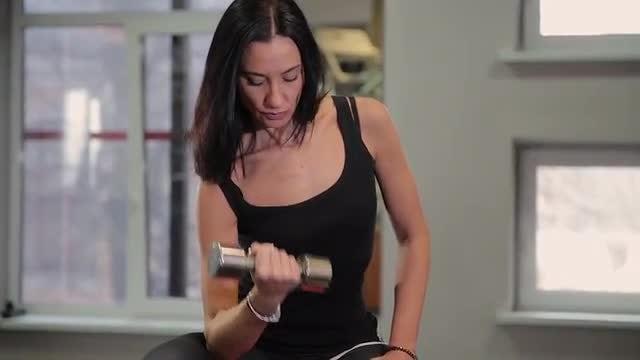 Woman Lifts Dumbbells: Stock Video