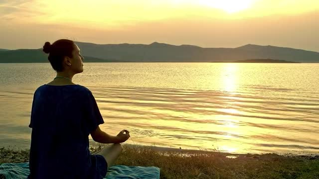 Meditating By A Lake: Stock Video
