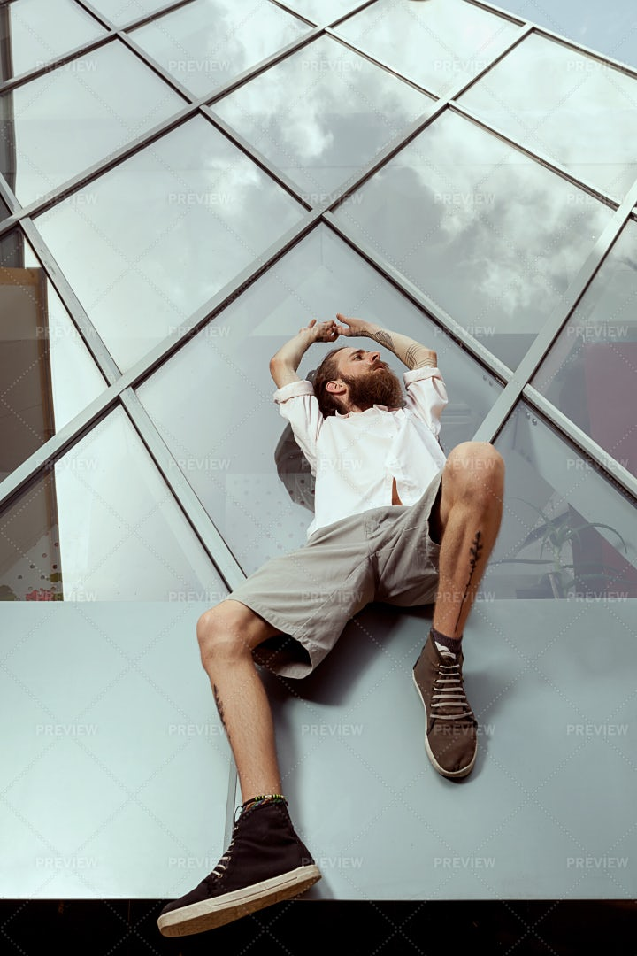 Man Reclines On Glass Building: Stock Photos