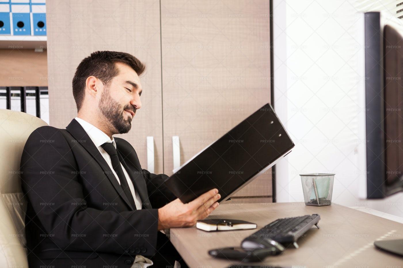 Businessman Smiles Over Sales Report: Stock Photos
