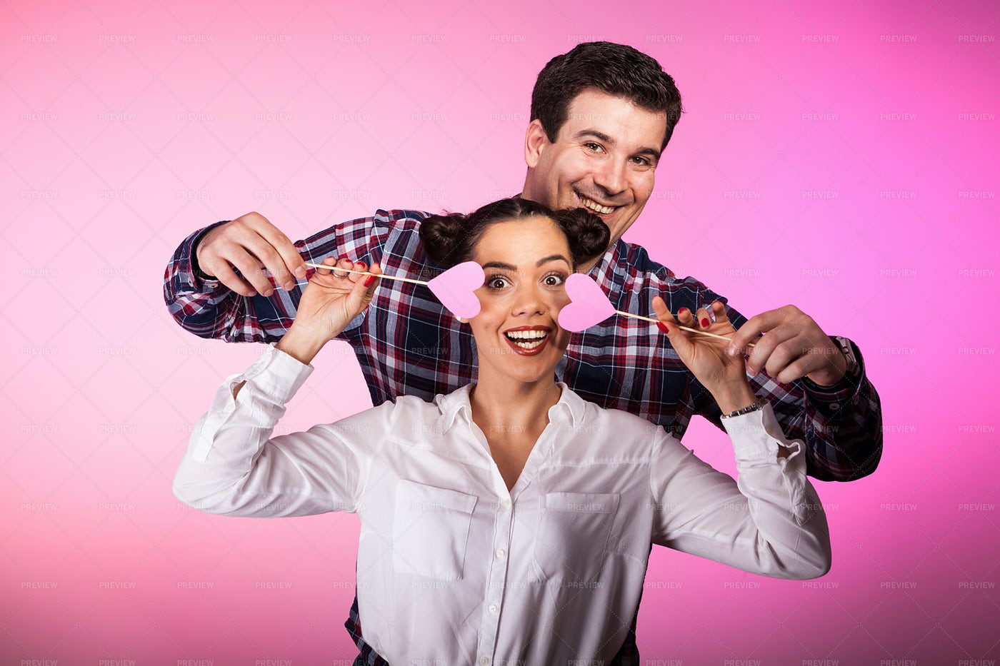 Couple In Studio With Two Pink Hearts: Stock Photos