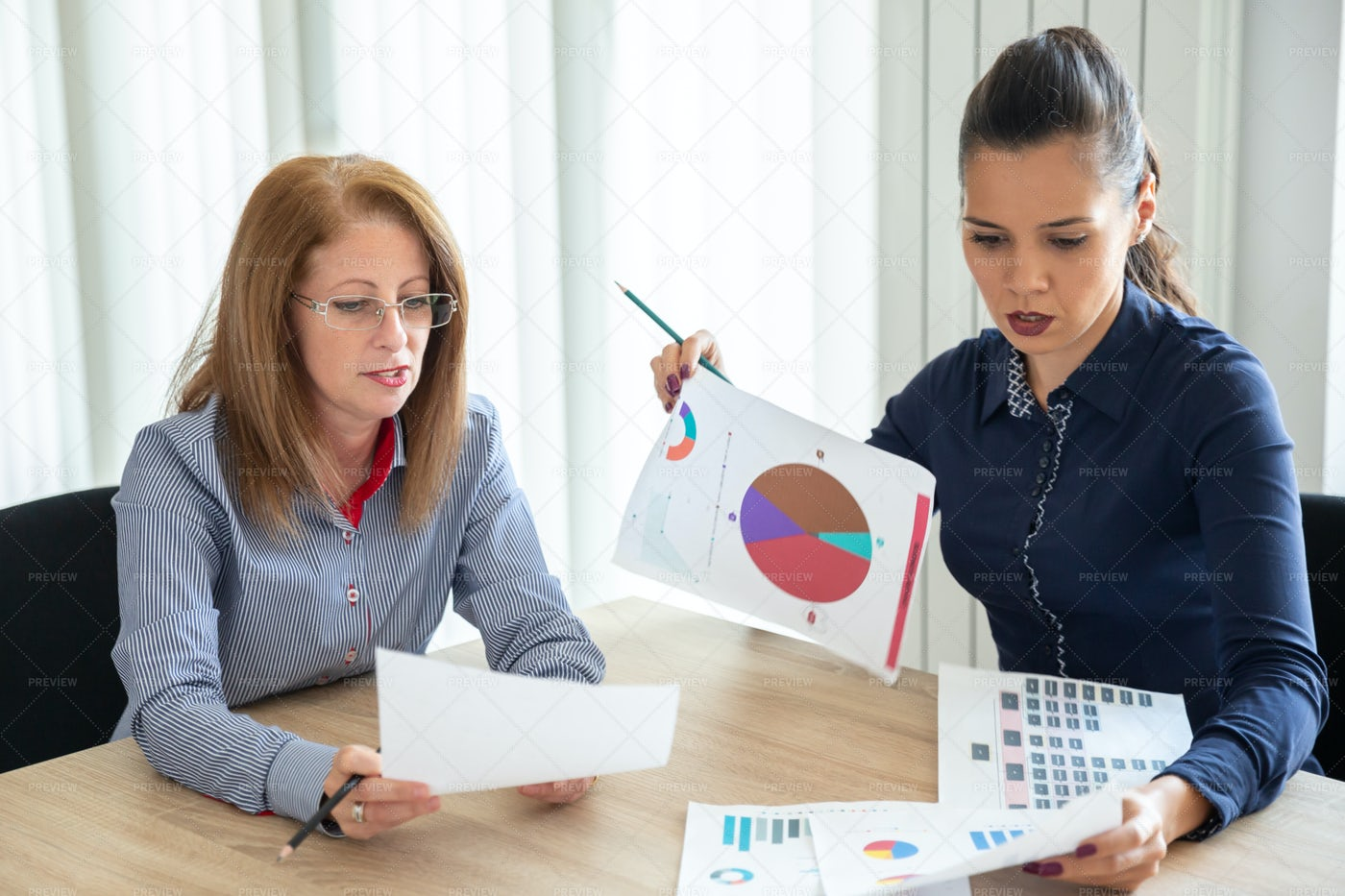 Colleagues Discuss Annual Report: Stock Photos
