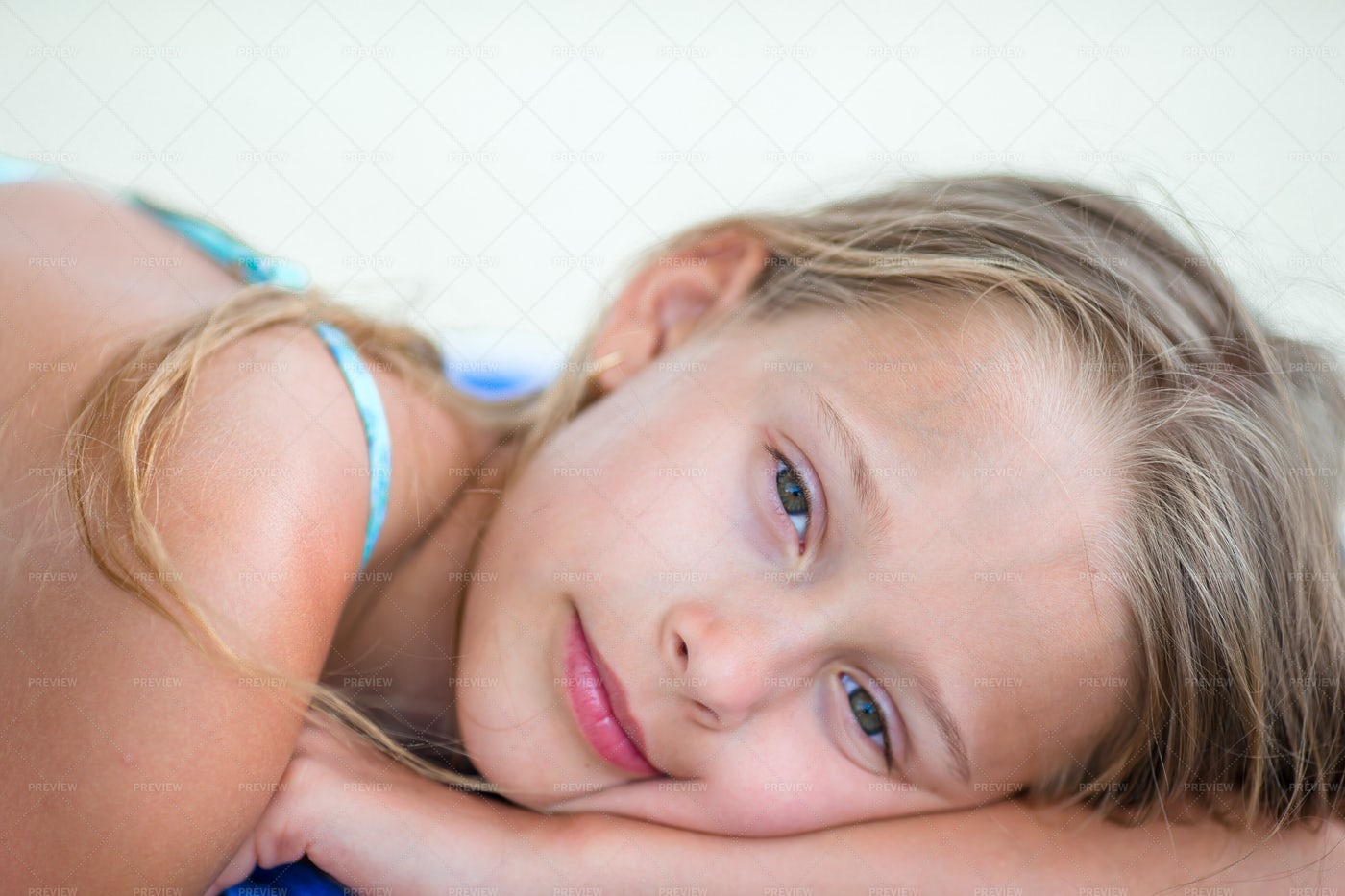 Portrait Of Girl Lying In The Sand: Stock Photos