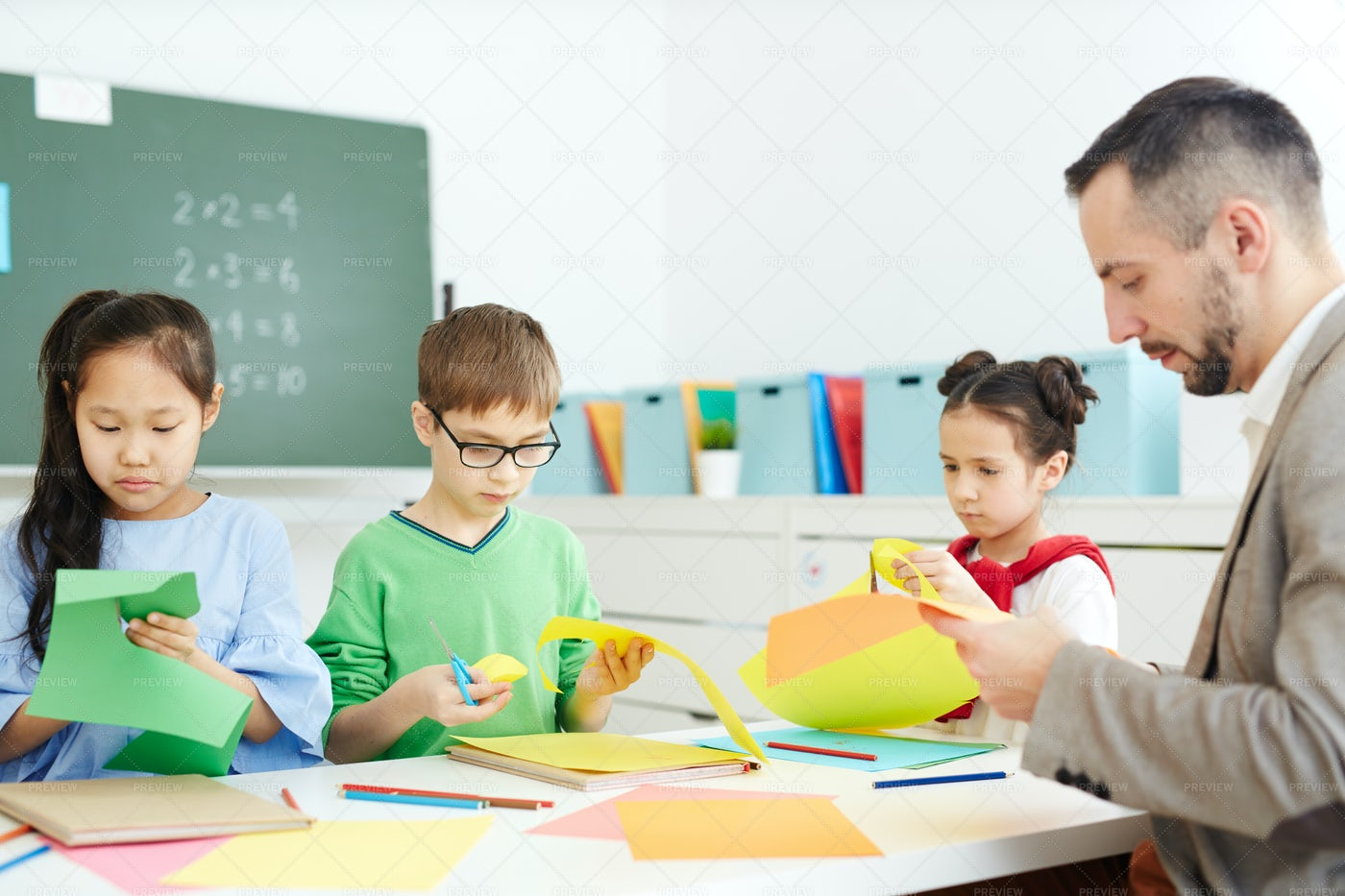 Kids Making Origami At School: Stock Photos