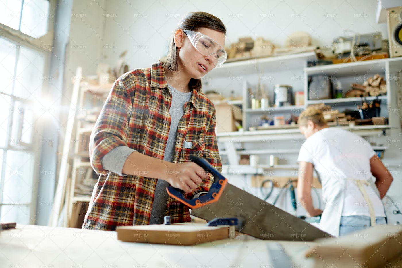 Female Woodworker Cutting Lumber Plank: Stock Photos