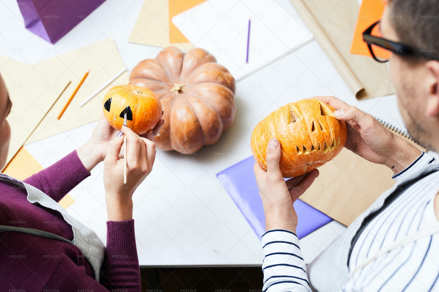Colleagues Carving And Painting Pumpkins: Stock Photos
