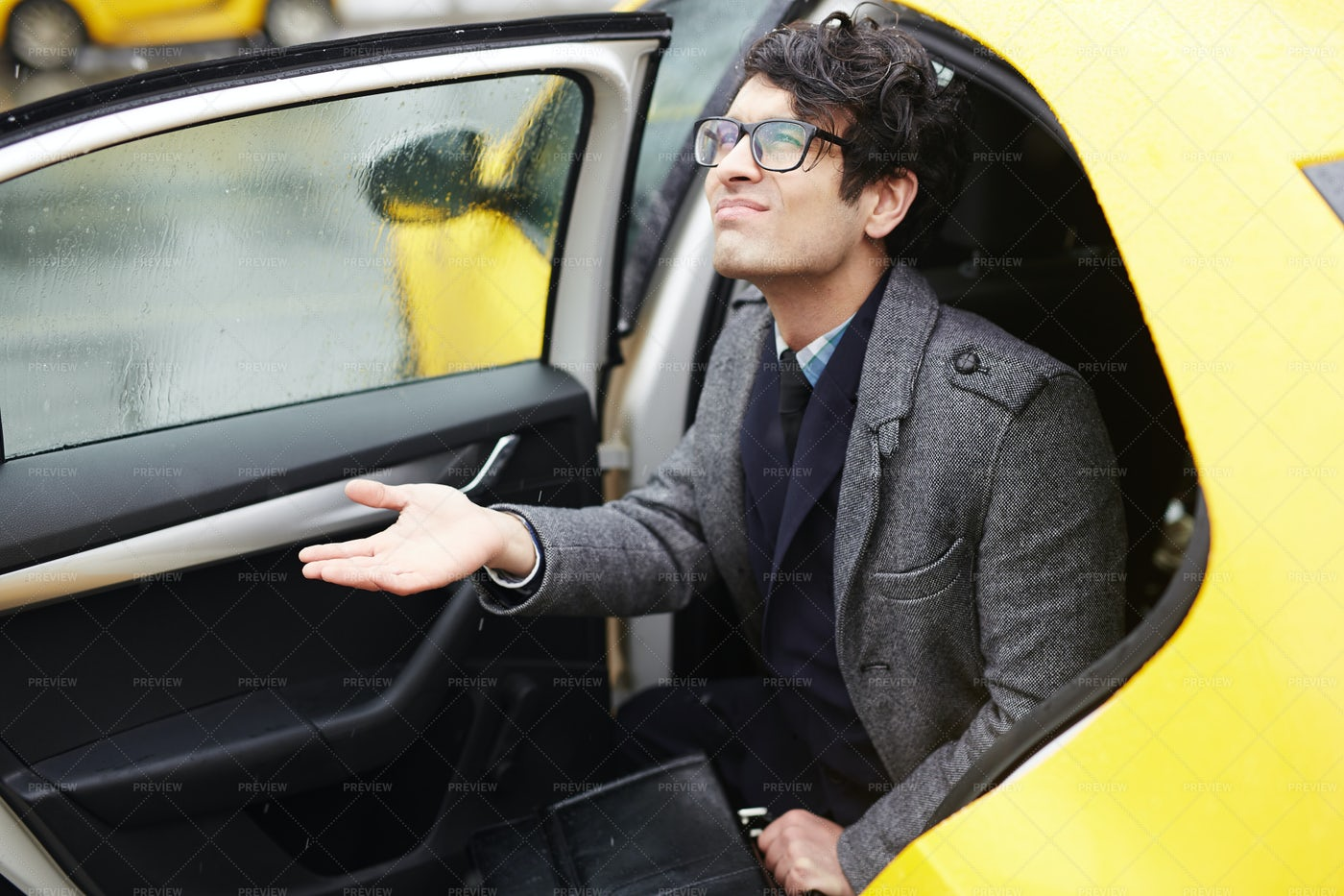 Young Businessman Leaving Taxi In Rain: Stock Photos