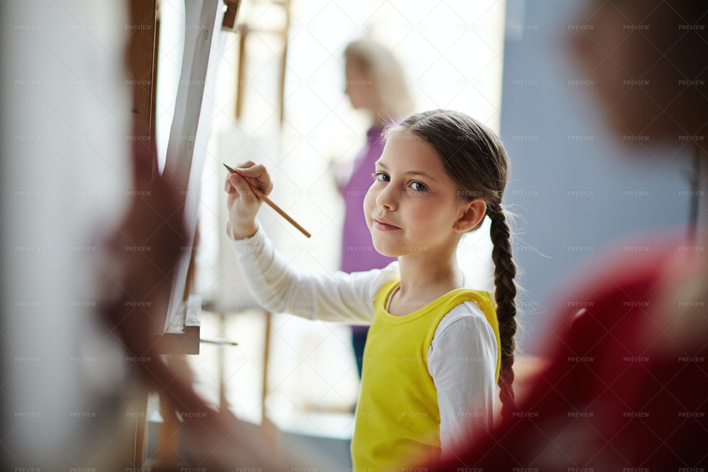 Kids Drawing On Easels In Art Class: Stock Photos