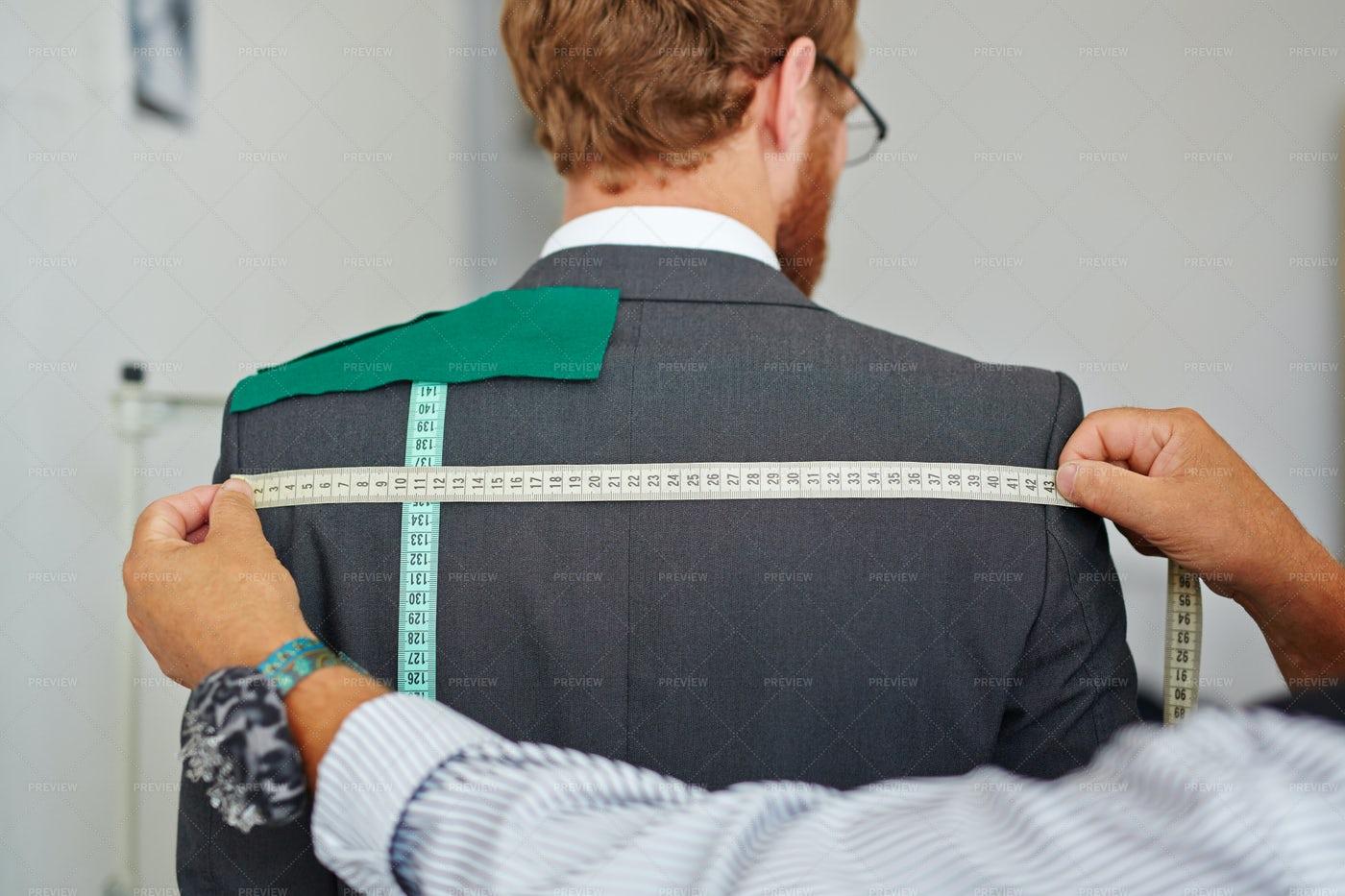 Tailor Taking Measurements On Customer: Stock Photos