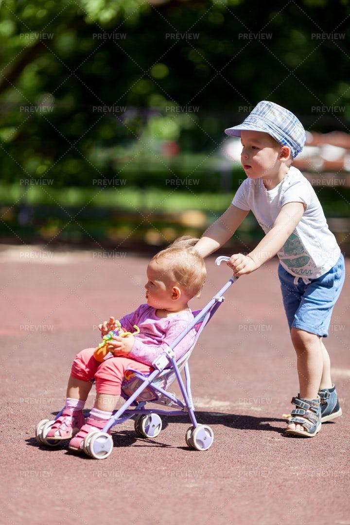 Boy Pushing Sister In A Stroller: Stock Photos