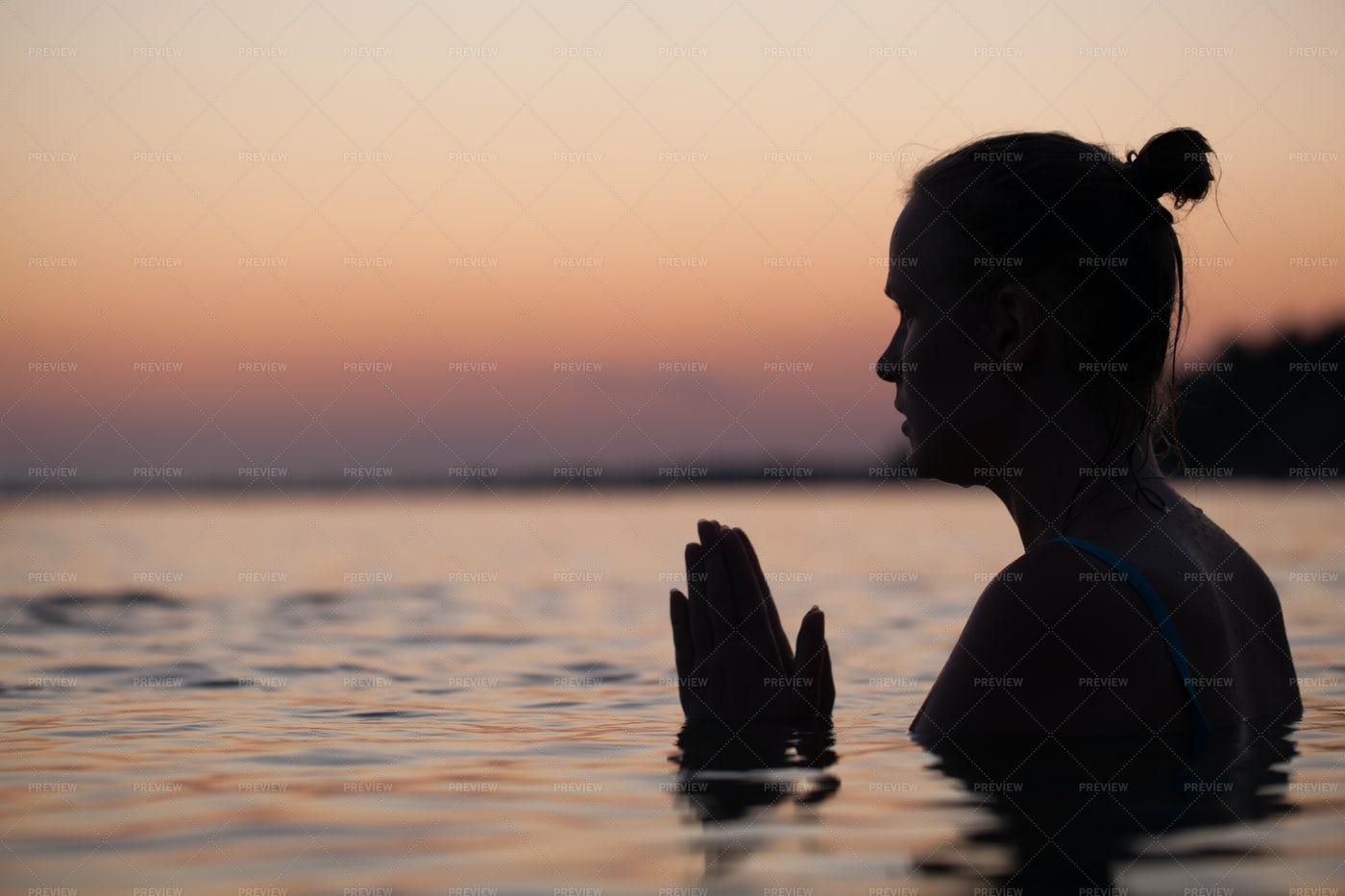 Woman In Water Praying Or Meditating: Stock Photos