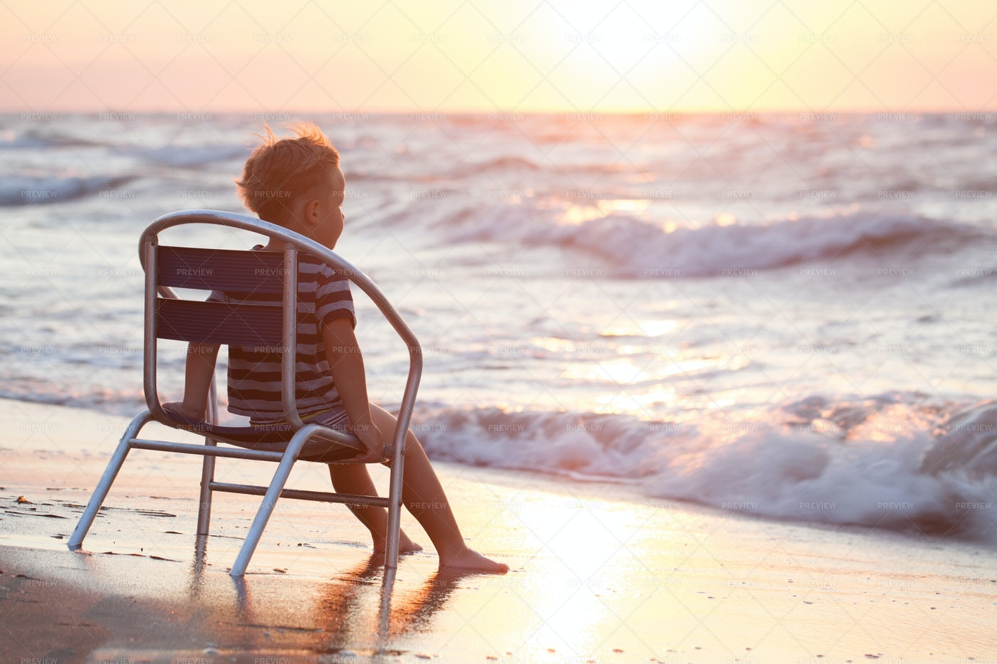 Boy Sitting On The Chair By Sea: Stock Photos